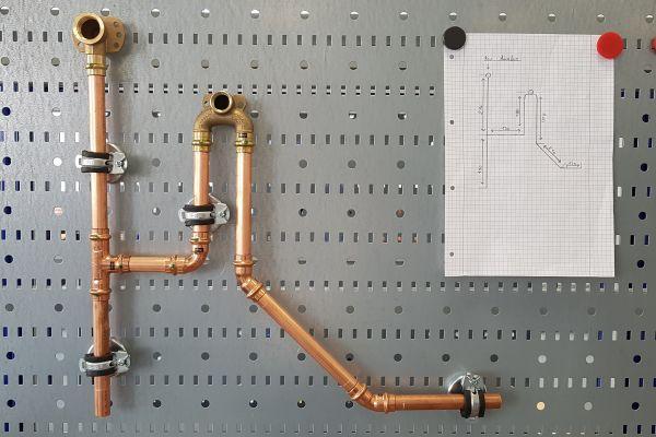 Zeichnung eines Rohrsystems neben einem echten Rohrsystem an einer Lernwand.