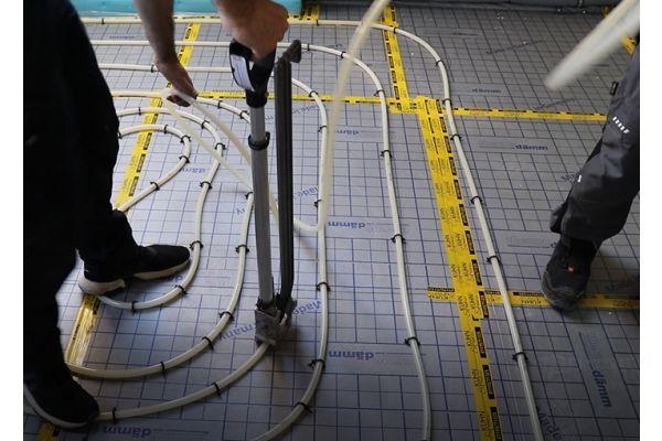 Ein Mann bedient ein Tackergerät zur Verlegung einer Fußbodenheizung.