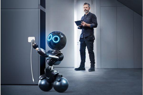 Ein Mann und ein Roboter stehen in einem Zimmer.