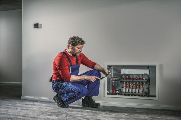 Ein Handwerker checkt einen Heizkreisverteiler mit einem Tablet.