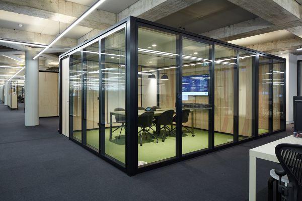 Ein Raum-in-Raum-System in einer offenen Bürofläche.
