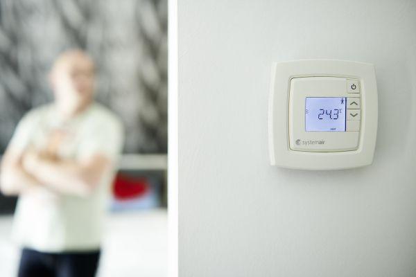 Ein Raumtemperaturregler an einer weißen Wand.