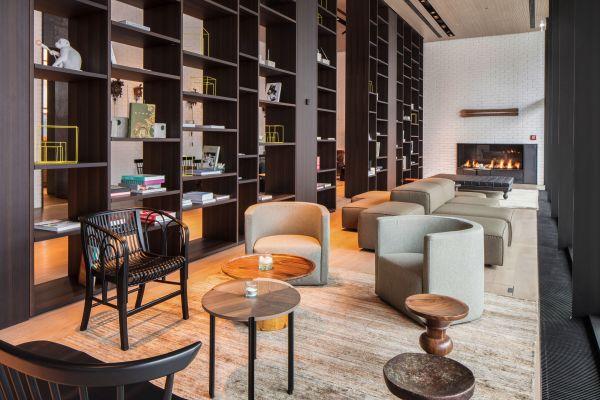 Ein Aufenthaltsraum mit Sesseln, Bücherregalen und einem Kamin.