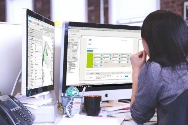 Eine Frau arbeitet an zwei Computer-Bildschirmen.