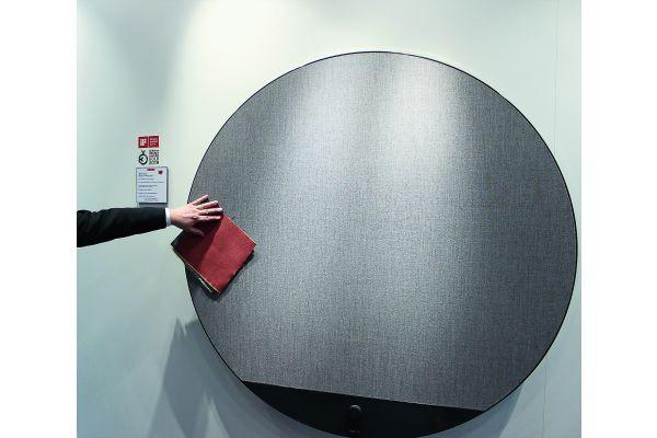 Runder Heizkörper an einer Wand, eine Hand hält ein Handtuch davor.