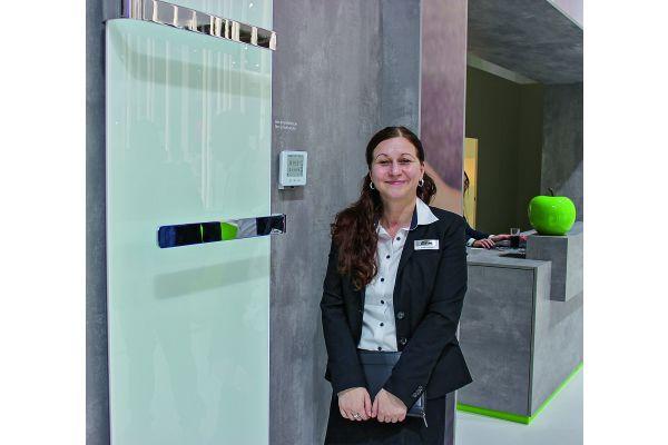 Eine Frau steht vor einem an einer Wand befestigten Design-Heizkörper.