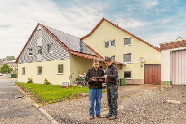 Zwei Männer stehen vor einem Haus und schauen auf ein Tablet.