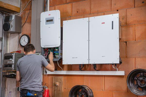 Ein Mann installiert einen Wechselrichter und einen Batteriespeicher.