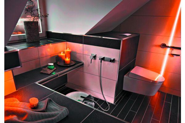 Das Bild zeigt einen Badezimmerausschnitt eines GGT-Musterbades, in dem sich unmittelbar neben der Wellnesszone eine Handbrause inklusive Bodenablauf befindet.