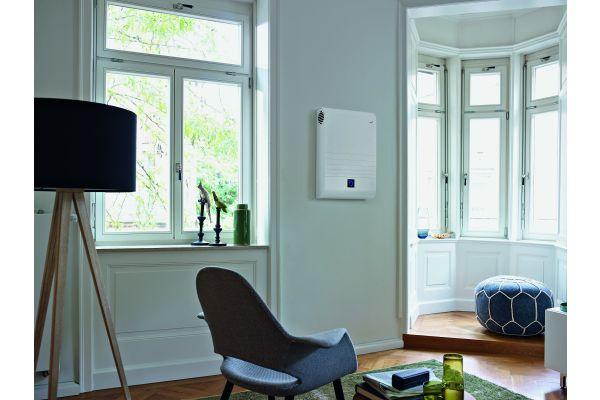 Das Bild zeigt ein Wohnzimmer, an dessen Wand das Lüftungsgerät