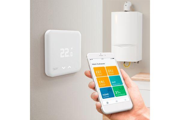 Smartphone, Brennwerttherme und Thermostat.