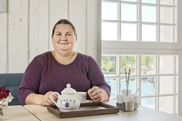 Eine Frau sitzt an einem Tisch, vor ihr eine Teekanne und Tasse.