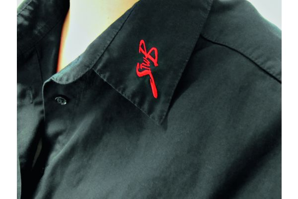 Das Bild zeigt ein schwarzes Hemd, auf dessen Kragen ein rotes Firmenloge gestickt wurde.