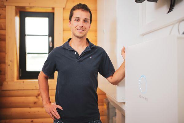 Ein Mann steht neben einem Stromspeicher.