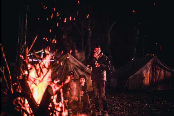 Ein Mann steht neben einem Lagerfeuer.