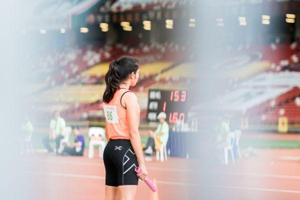 Eine Staffelläuferin steht auf einer Laufbahn in einem Stadion.