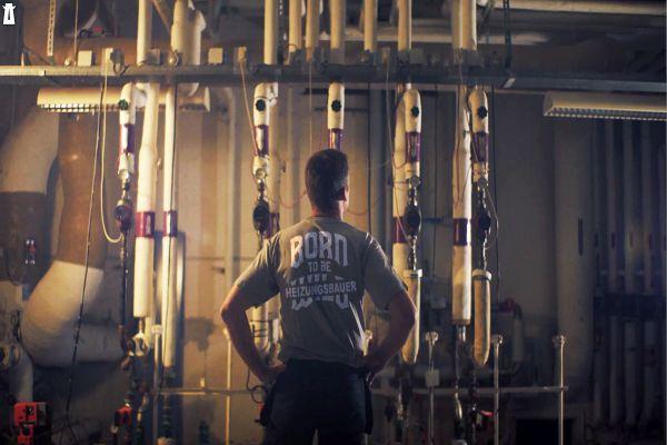 Ein Mann steht vor den Rohren einer Heizungsanlage.