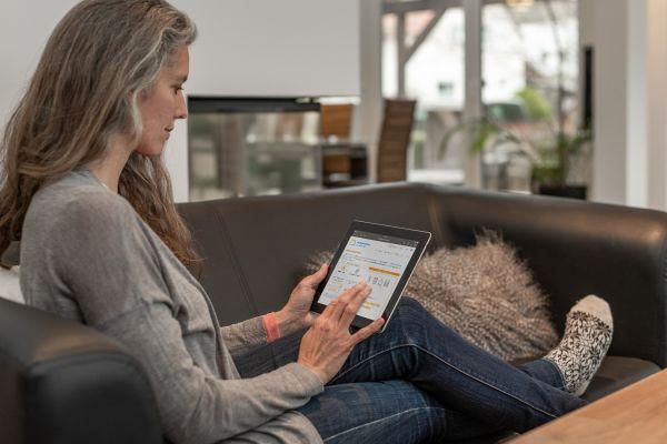 Eine Frau sitzt mit einem Tablet auf einem Sofa.
