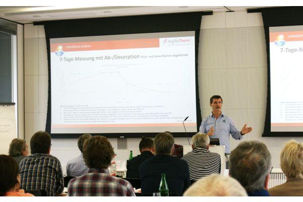Ein Mann hält vor einer Leinwand mit einer Powerpoint-Präsentation einen Vortrag.