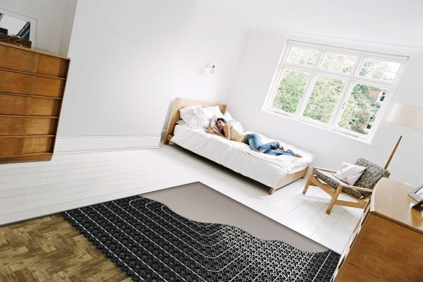 Ein Schlafzimmer mit einem Bett, der halbe Fußboden ist noch offen und zeigt die Bestandteile der Fußbodenheizung.