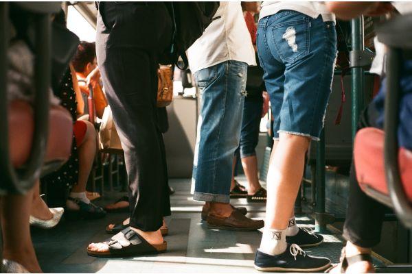 Die Füße von stehenden Passagieren in einer Straßenbahn.
