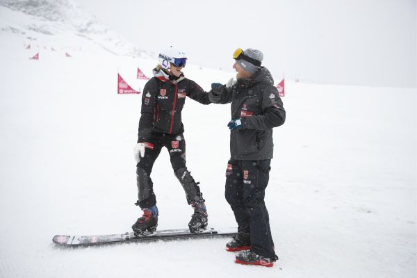 Das Bild zeigt zwei Snowboardfahrer im Schnee.