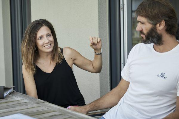 Foto einer Frau und eines Mannes, die nebeneinander an einem Gartentisch sitzen.