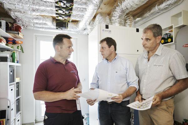 Drei Männer stehen vor einer Wärmepumpe.
