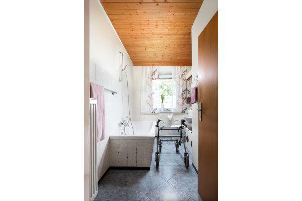 Ausgangssituation: Badezimmer mit Badewanne und hohem Einstieg. Durch den schmalen Grundriss ist das Bad mit Gehhilfe oder Rollstuhl nicht benutzbar.
