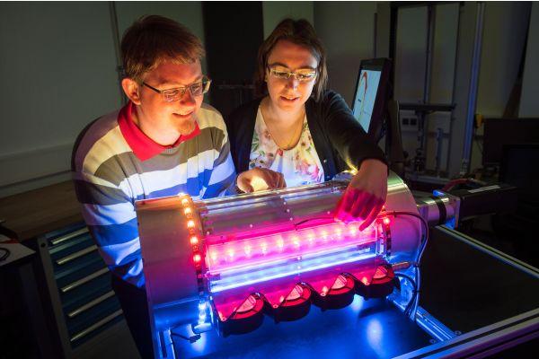 Ein Mann und eine Frau stehen vor dem Prototyp einer Kältemaschine nach dem elastokalorischen Effekt.