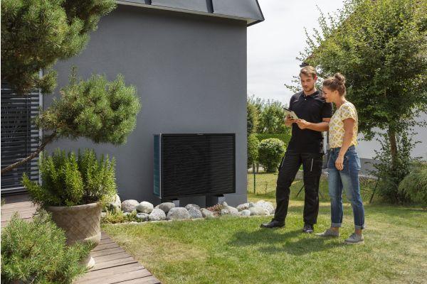 Ein Mann und eine Frau stehen in einem Garten neben einer Wärmepumpe.