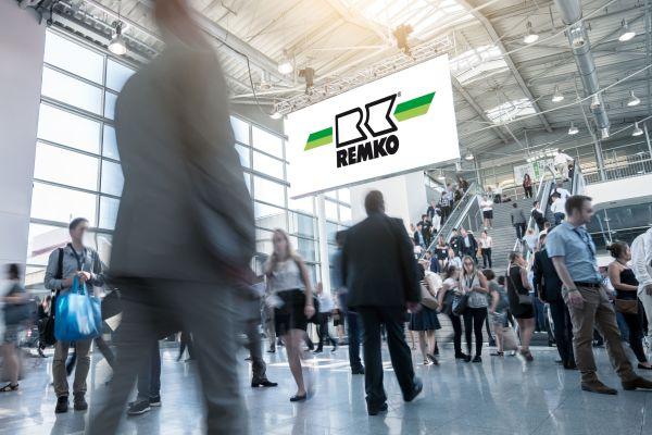 Menschen laufen durch eine Halle, oben in der Mitte ist das Logo von Remko zu sehen.
