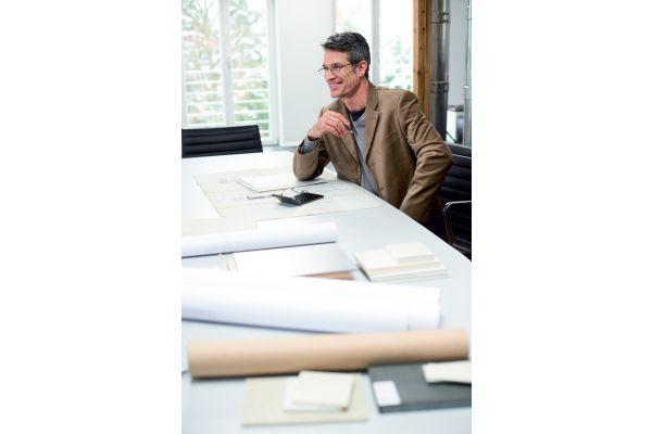 Ein Mann sitzt an einem Tisch, neben ihm liegen Papierrollen.