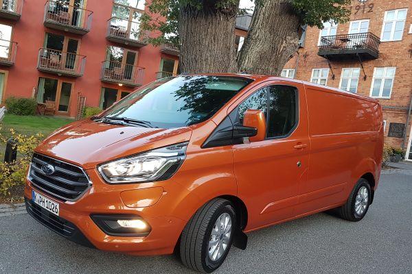 Ein orangener Ford Transit Custom PhEV.