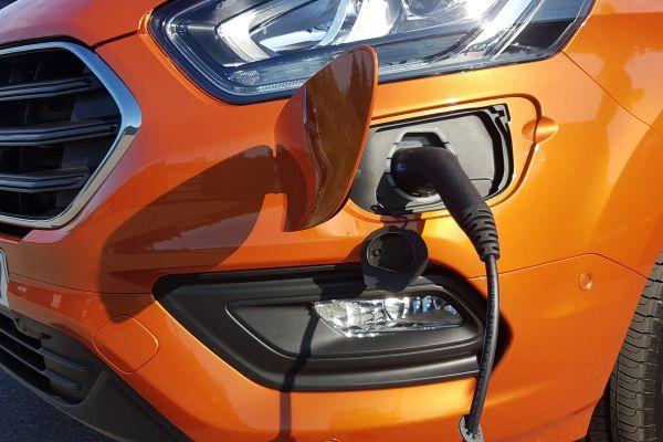 Stoßfänger an einem Auto mit Anschlussmöglichkeit zum Laden einer Batterie mit angeschlossenem Ladekabel.