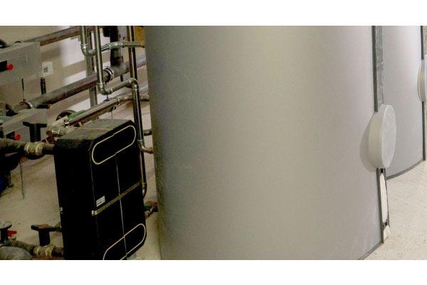 Wärmeübertrager und Warmwasserspeicher in einem Heiztechnikraum.
