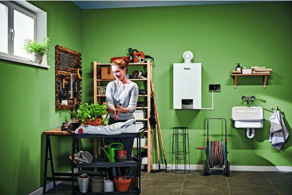 Eine Frau arbeitet in einem Kellerraum, rechts an der Wand hängt eine Gastherme.