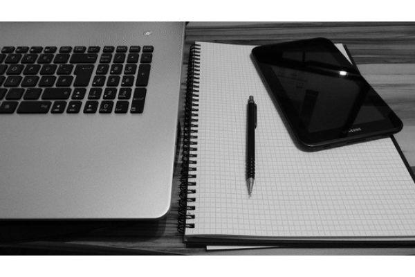 Das Bild zeigt einen Notizblock neben einem Laptop.
