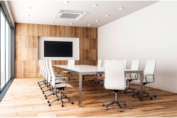 Ein Besprechungsraum mit großem Tisch und Stühlen.