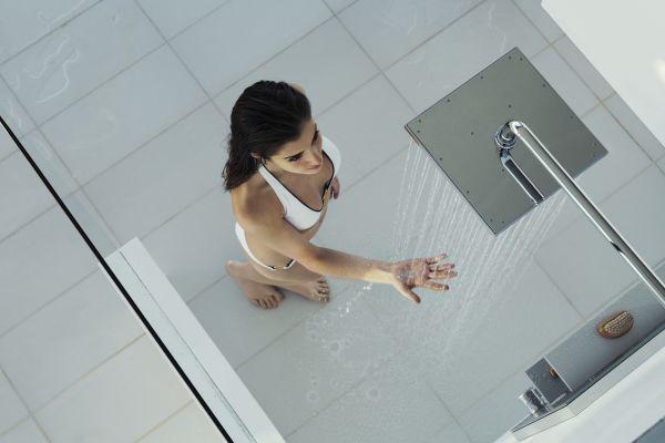Das Bild zeigt eine Frau im weißen Bikini von oben, die ihre Hand in das Wasser hält, das aus der Kopfbrause von Keuco fließt.