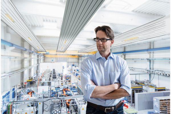 Ein Mann steht in einer Industriehalle, im Hintergrund sind Deckenstrahlplatten zu sehen.