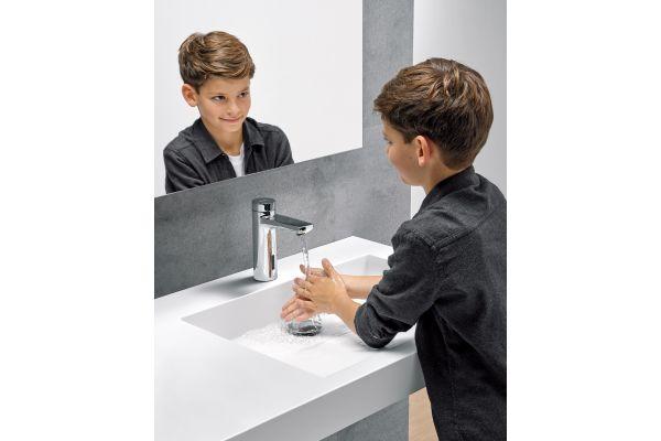 Das Bild zeigt einen Jungen, der sich die Hände wäscht.