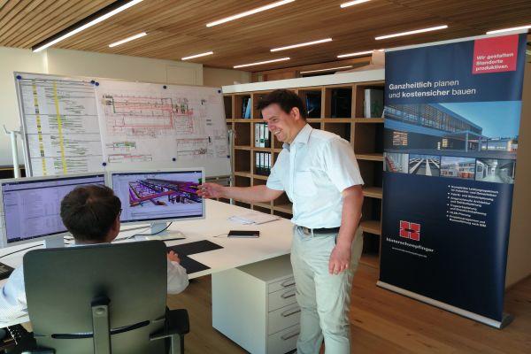 Ein Mann sitzt vor zwei Computer-Bildschirmen an einem Schreibtisch, daneben steht ein zweiter Mann.