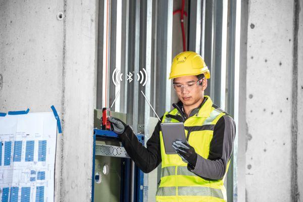 Eine Frau auf einer Baustelle benutzt ein Laser-Distanzmessgerät.