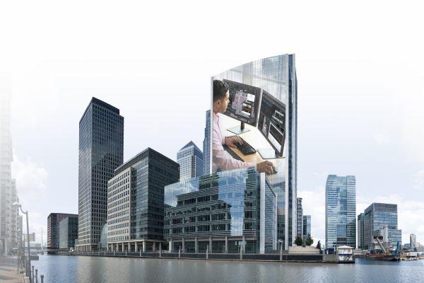 Fotocollage aus Gebäuden und einem Mann, der vor zwei Computer-Bildschirmen an einem Schreibtisch sitzt.