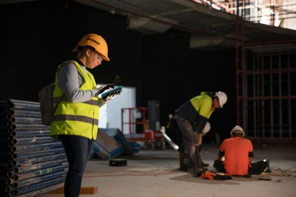 Eine Frau mit Schutzkleidung blickt auf einer Baustelle auf ihr Smartphone, zwei Männer befinden sich im Hintergrund.
