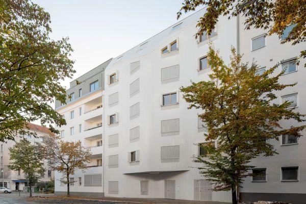 Ein weißes, mehrstöckiges Gebäude an einer Straße.