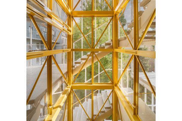 Fahrstuhl mit gelber Streckmetallverkleidung.