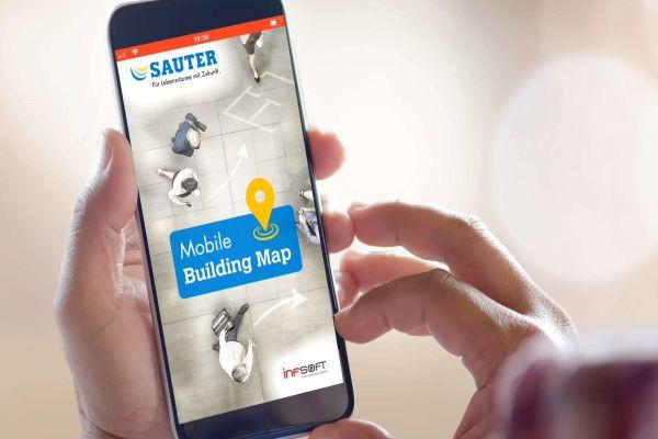 Eine Hand hält ein Smartphone mit geöffneter Mobile Building Map-App.
