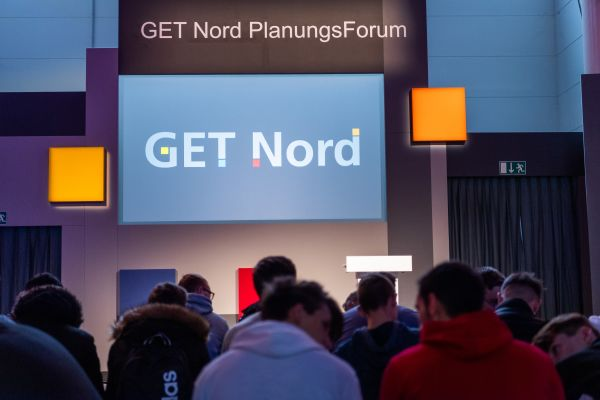 Ein Bildschirm mit der Aufschrift GET Nord in einer Messehalle mit Besuchern.